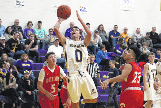 Southern senior Dylan Smith (0) goes up for a shot in between Rebels Curtis Haner (5) and Bryce Nolan (23), during the Tornadoes' 88-41 victory on Friday in Racine, Ohio.