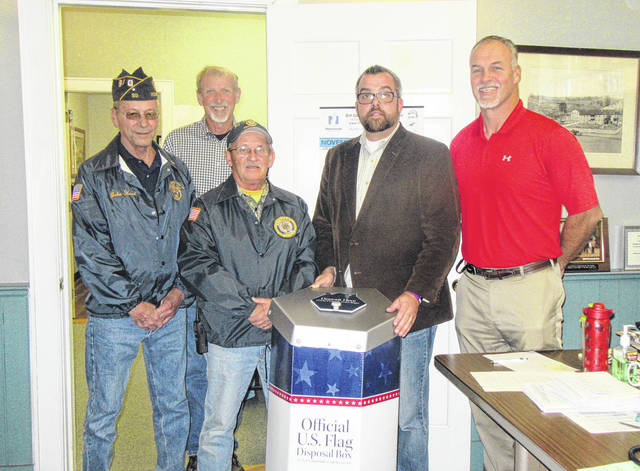 Commissioners Tim Ihle, Randy Smith and Mike Bartrum welcome an American Flag disposal box from Drew Webster American Legion Post 39 members John Hood and Bill Spaun.