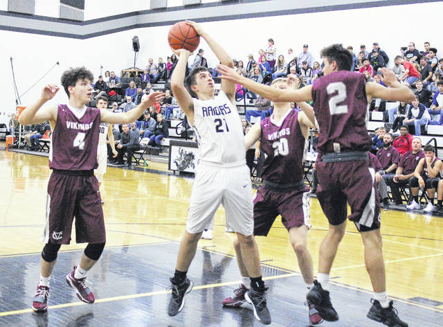 River Valley sophomore Matthew Mollohan (21) releases a shot attempt between a trio of Vinton County defenders during the first half of Tuesday night's TVC Ohio boys basketball contest in Bidwell, Ohio.