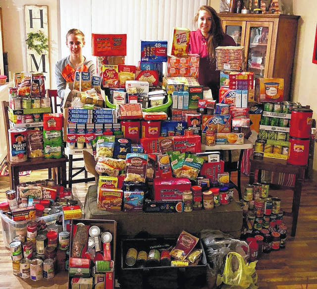 Payton VanInwagen and Heather Brooks are pictured with some of the donations for the Veteran's Outreach food pantry. Brooks said that all of the donations would not fit in one photo.