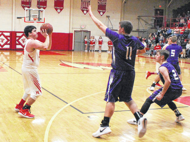 Wahama junior Tyler Bumgarner, left, releases a three-point attempt during the first quarter of Friday night's TVC Hocking boys basketball contest against Miller in Mason, W.Va.