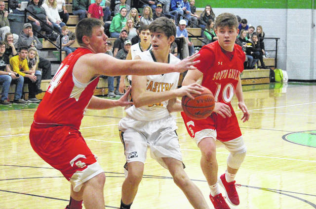 Eastern sophomore Garrett Barringer (center) fights through a double team set by Rebels Austin Day (left) and Eli Ellis (10) during the Eagles' 64-43 victory on Tuesday in Tuppers Plains, Ohio.