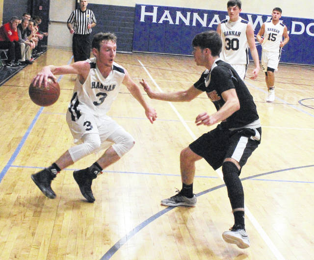 Hannan senior Malachi Cade (3) tries to dribble around a Wayne defender during the second half of Thursday night's non-conference boys basketball contest in Ashton, W.Va.
