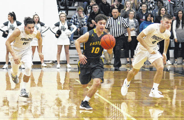 Eastern junior Sharp Facemyer (center) leads RVHS seniors Dustin Barber (left) and Jarret McCarley (right) on a fast break, during the Eagles' 56-41 victory on Friday in Bidwell, Ohio.