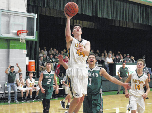 Eastern senior Kaleb Hill (44) shoots a layup in front of teammate Colton Reynolds (14) and Bobcats Gage Sampson (2) and Caden Blizzard (1), during the second half of the Eagles' 63-61 setback on Thursday in Tuppers Plains, Ohio.