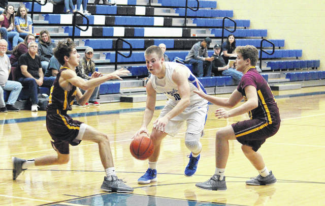 Gallia Academy junior Justin McClelland (center) drives in between Marauders Cole Betzing (left) and Nick Lilly (right), during the first half of the Blue Devils' 59-37 victory on Tuesday in Centenary, Ohio.