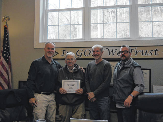 Commissioners Mike Bartrum, Randy Smith, and Tim Ihle present Paul Gerard with a service award.