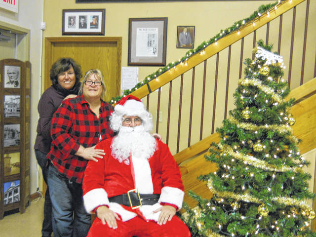 Kids' Corner volunteers Debbie Pratt and Debbie Weber with Santa Claus (Steven Figiel).