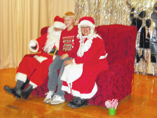 Mr. Claus (Brian Howard) and Mrs. Claus (Teresa Shiflet) with a boy from the nice list.
