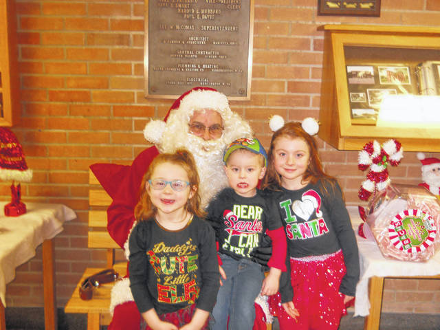 """Middleport Village Building Inspector Mike Hendrickson dressed as Santa Claus listens to Lucas, Brynleigh, and Addison Anderson's Christmas wishes. Children in the village got to meet with """"Santa"""" this week in Middleport, making sure he knows where to leave those presents on Monday."""