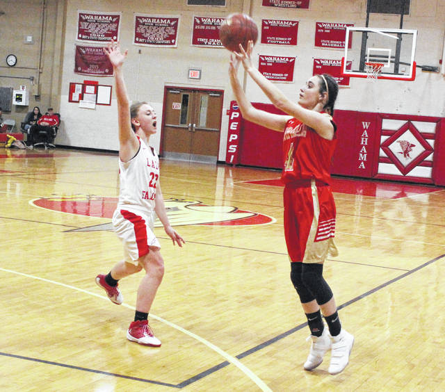 South Gallia sophomore Kiley Stapleton, right, releases a shot attempt over Wahama defender Elizabeth Mullins during the first half of Thursday night's TVC Hocking girls basketball contest at Gary Clark Court in Mason, W.Va.