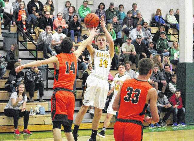 Eastern sophomore Colton Reynolds (center) pulls up for a jump shot, during the first half of the Eagles' 55-34 victory over Nelsonville-York on Wednesday in Tuppers Plains, Ohio.