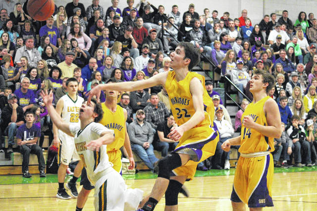 Southern junior Brayden Cunningham (23) blocks a Sharp Facemyer (left) shot attempt in front of SHS sophomore Trey McNickle (14), during the first half of the Tornadoes' six-point win on Friday in Tuppers Plains, Ohio.