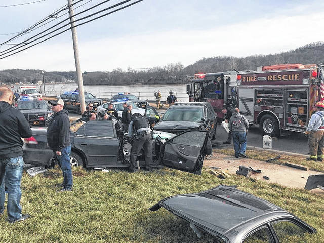First responders investigate a suspect vehicle after extricating its victims on the 600-block of Pomeroy's East Main Street, the result of a collision with a Meigs deputy.