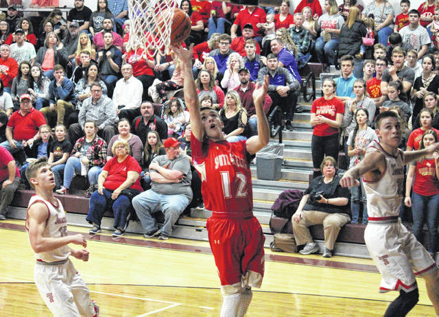 South Gallia senior Austin Stapleton (12) shoots a two-pointer in between Tomcats Cameron Kittle (left) and Randy Hixson (right), during Trimble's 71-58 victory on Tuesday in Rocksprings, Ohio.