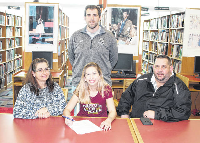 Point Pleasant senior Caitlin Peal, seated front and center, will be continuing her soccer career after signing a letter of intent with the University of Charleston on Thursday at the PPJSHS library in Point Pleasant, W.Va. Caitlin, a three-year starter for the Lady Knights, is joined by her parents Christy and Dave Peal, with PPHS girls soccer coach Chris Errett standing in back.