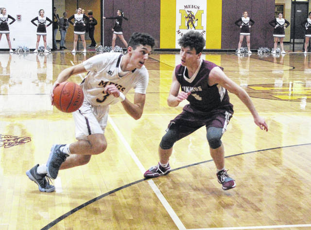 Meigs sophomore Weston Baer, left, dribbles past a Vinton County defender during the first half of a Jan. 26 TVC Ohio boys basketball contest in Rocksprings, Ohio.
