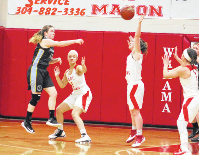 OVCS junior Emily Childers, left, throws a pass over the Wahama defense during a Feb. 15 girls basketball contest at Gary Clark Court in Mason, W.Va.