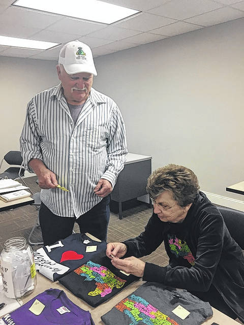 Bob Graham is pictured with Mary Cowdrey, winner of the raffle prize, a Morgan Silver Dollar.