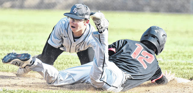 River Valley shortstop Chase Barber attempts a tag on a sliding Alexander runner during Friday night's 15-9 loss to the Spartans in Bidwell, Ohio.