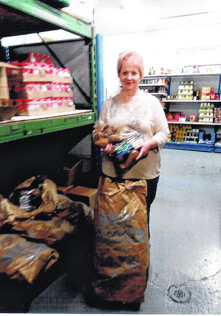 Hilda Weaver, Key Volunteer at the Meigs Cooperative Parish Food Pantry, holds a bag of potatoes recently donated to the Food Pantry.