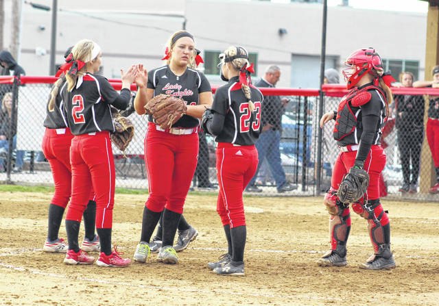 Point Pleasant senior Leah Cochran, standing in middle, receives congratulations from teammate Peyton Jordan (2) and other infielders following a strikeout in an April 25 non-conference softball contest against Ripley in Point Pleasant, W.Va.