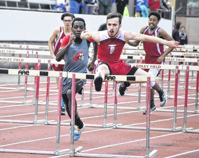 Wahama's Brodee Howard clears an obstacle as Point Pleasant's Kaydean Eta gives chase during the 110-meter hurdles event held Friday, March 30, at Laidley Field in Charleston, W.Va.