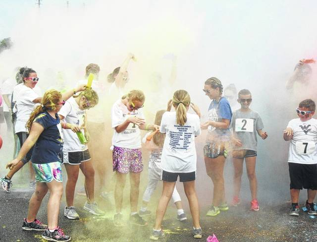 Participants in the color run were covered in various shades of blue, pink, yellow and purple as they prepared for the event with more colors added along the way.