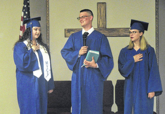 Mid-Valley Christian School graduates (from left) McKensie Boso, Tyler Peyton and Abi Puariea lead the pledges during the graduation ceremony on Friday evening.