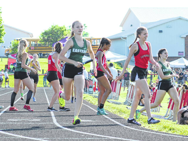 Eastern freshman Ashton Guthrie takes off after receiving the baton from teammate Rhiannon Morris, right, during the third leg of the Division III Region 11 4x800m relay final held Wednesday night at Fairfield Union High School in Lancaster, Ohio.