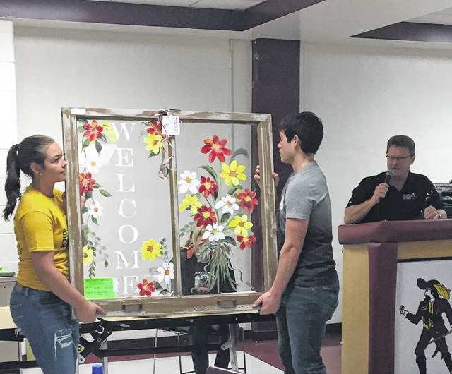 An old Meigs County Courthouse window was painted by Michelle Musser and donated by Tim Ihle as an auction item. It was displayed by members of the Eastern High School National Honor Society.