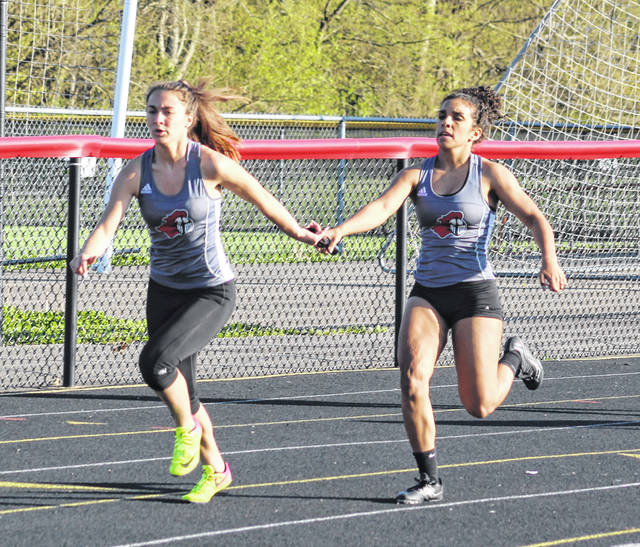 The Point Pleasant duo of Teagan Hay and Sydnee Moore complete a baton exchange in the 4x200m relay event on Monday night at the 2018 Battle for the Anchor at Ohio Valley Bank Track and Field in Point Pleasant, W.Va.