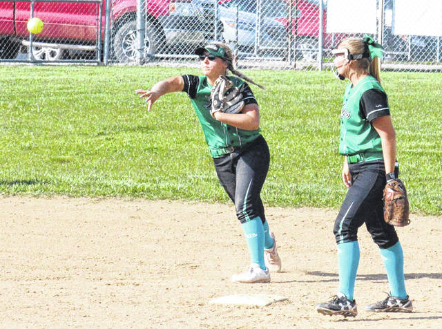 Eastern senior Sidney Cook (left) throws to first base in front of teammate Cera Grueser (right), during a non-conference softball game on May 7 in Tuppers Plains, Ohio.