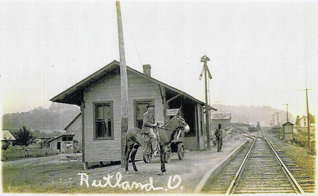 This undated photo shows a donkey and his rider at the Train Depot in Rutland, as another man stands in the background waiting for the train.