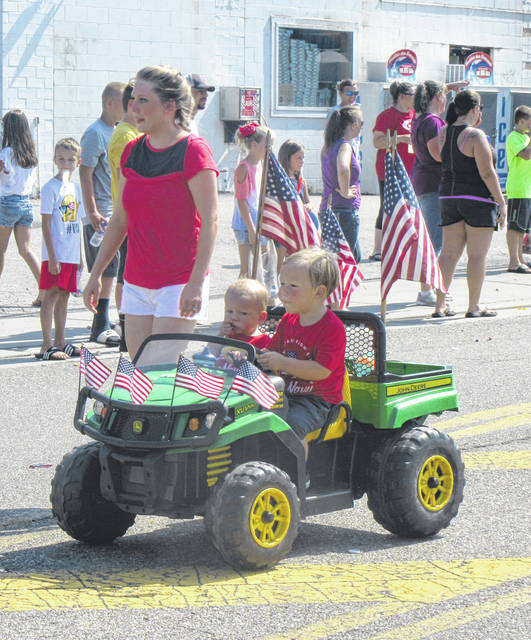 Leo and Max Poole drive along the parade route in Racine on Wednesday morning.
