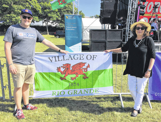Madog Center Davis Intern Dan Rowbotham and Director Jeanne Jones Jindra display the Rio Grande village flag during Cymru-Ohio 2018 celebration.