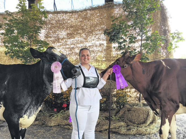 Sydney Zirkle is pictured with her overall grand and reserve champion dairy cows.