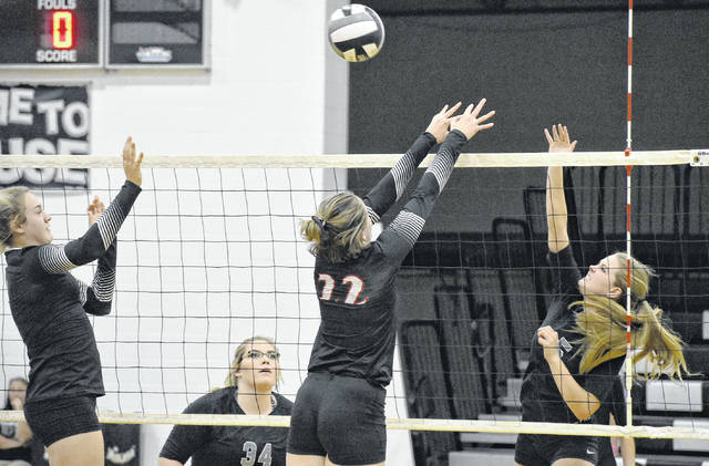 RVHS senior Rachel Horner attempts a spike over two Lady Oaks defenders during the Lady Raiders' win on Wednesday night in Bidwell, Ohio.