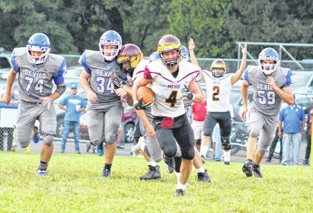 Meigs freshman Ty Bartrum (4) breaks away from a trio of Gallia Academy defenders during the first half of a Week 1 football contest at Memorial Field in Gallipolis, Ohio.