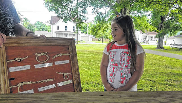 Layla Nibert, Daisy Girl Scout Troop 1006, demonstrates her knot board that she made with her Grandpa.