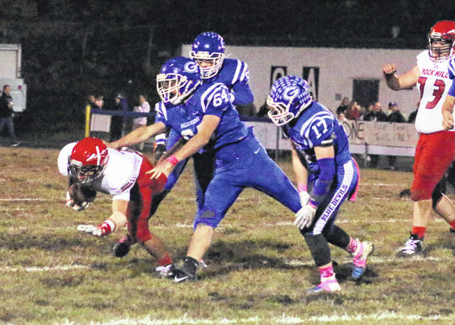 Gallia Academy freshman Brayden Easton (64) shoves Rock Hill running back Zak Adkins to the ground during the first half of Friday night's 43-20 victory in a Week 8 Ohio Valley Conference matchup at Memorial Field in Gallipolis, Ohio.