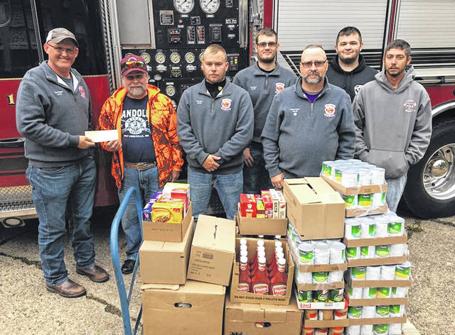 "The 2018 Pomeroy Firemen's Association ""Feeding Our Friends"" food drive was held on Saturday, Oct. 13. With the help of our community, the firemen's association donated 1,056 food items along with $1,039.06 to the Meigs Cooperative Parish. Both numbers are records for the 6th annual drive, which is held at Powell's Foodfair. Pictured are representatives from the Pomeroy Firemen's Association presenting a portion of the donated non-perishable food items along with a check to a representative from the Meigs Cooperative Parish."