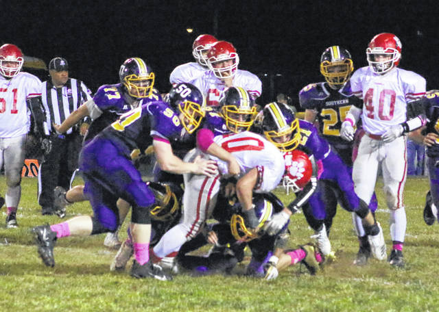 Southern defenders Alex Vanmeter (50), Auston Colburn (77) and Austin Baker (21) combine to bring down Trimble running back Conner Wright during a first half run Friday night in a Week 9 TVC Hocking football contest at Roger Lee Adams Memorial Field in Racine, Ohio.