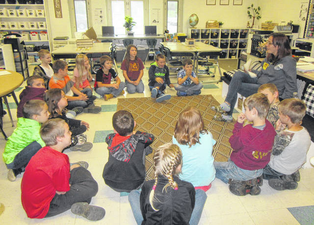 Tiffani Jacks talks with students in Joy Hysell's third grade classroom at Meigs Elementary.