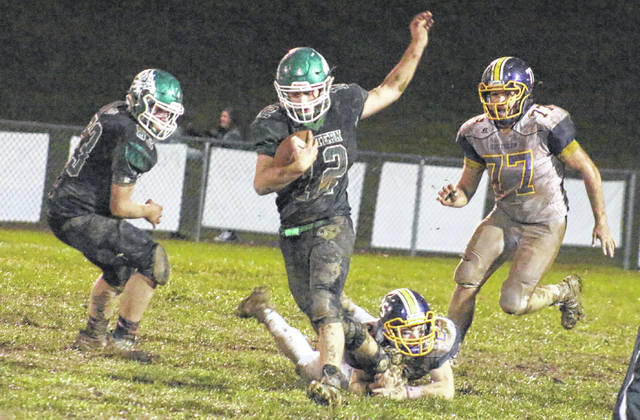 Eastern senior Blaise Facemyer (12) slips the grasp of Southern senior Reece Reuter (25), during the Eagles' 27-26 victory on Saturday in Tuppers Plains, Ohio.