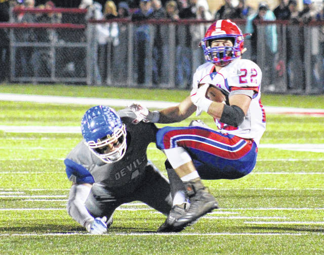 Gallia Academy senior Jacob Campbell knocks Licking Valley running back Connor McLaughlin down for a loss during a Division IV, Region 15 playoff contest at Alumni Stadium in Jackson, Ohio.
