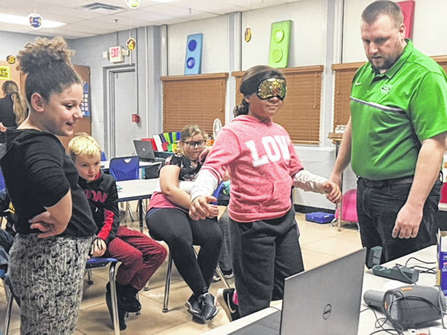 "Dr. Steven Leigh, assistant professor of biomechanics at Marshall University, teaches students about force and balance. Leigh and Dr. Suzanne Konz traveled to New Haven Elementary to present their ""Biomechanics Roadshow"" to students."