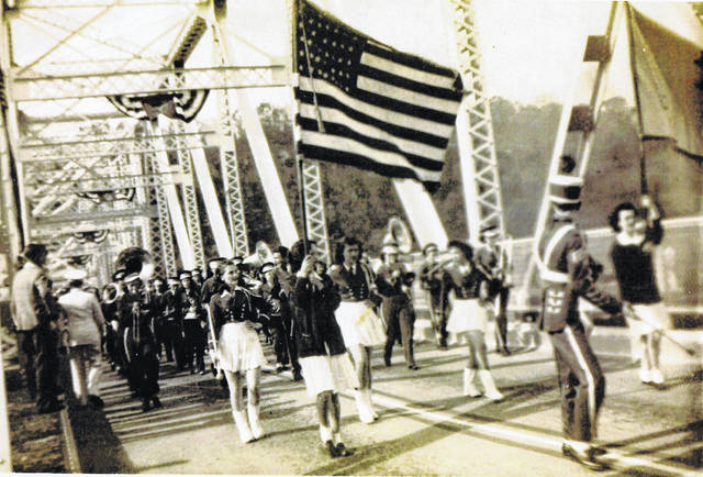 The 1946 Pomeroy High School Marching Band makes its way across the Pomeroy-Mason Bridge. The band is led by Drum Major Bob Hawley, according to a note written on the photograph. While it is clear from the flag and banner that the event which the band was taking part in was a patriotic celebration, it is not known which holiday or event the band was celebrating.