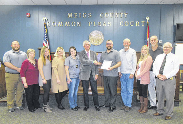 Judge I. Carson Crow, center, was recognized during the recent meeting of the Meigs County Commissioners. He is pictured along with Common Pleas Court staff and Commissioners. Pictured, from left, are Cassady Wilford, Karen Werry, Amanda Reed, B.J. Kreseen, Courtney Bullington, Crow, Randy Smith, Tim Ihle, Andrea VanInwagen, Mike Bartrum and Steve Jagers.