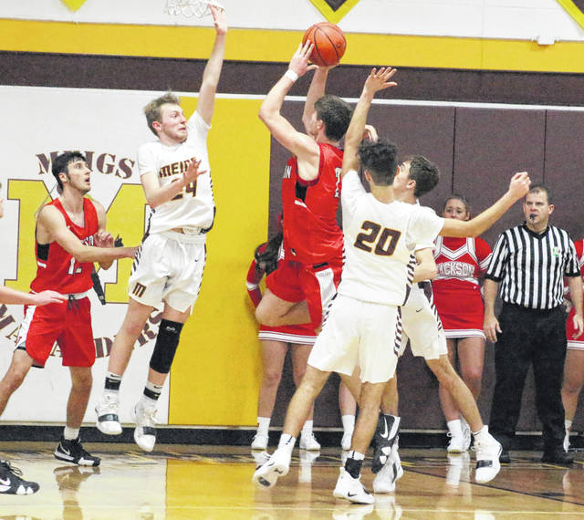 Meigs defender Cooper Darst (24) contests a shot attempt by Jackson's Traylen Davis during the second half of Friday night's non-conference boys basketball contest at Larry R. Morrison Gymasnium in Rocksprings, Ohio.
